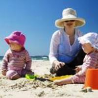 woman and two small children on a beach