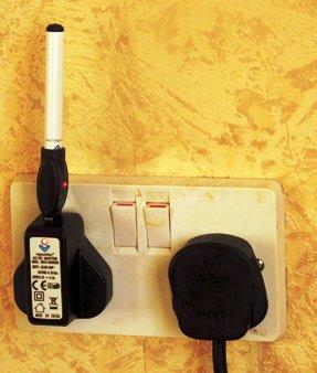 an e-cigarrette re-charging in a wall socket