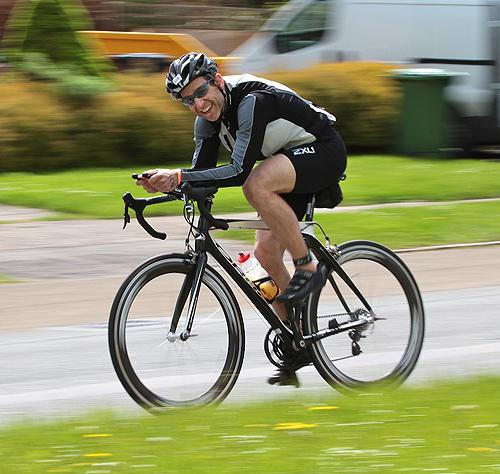 A competitor manages a smile as he whizzes down Whittlebury High Street towards Silverstone
