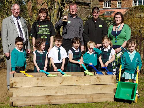 Richard Edwards, Headteacher at Nicholas Hawksmoor with Kathryn Hunter, Start Wise, manager of Homebase, Victoria Shepherd and Jess White, Alotment Club Leader and teacher, together with some children from nursery and reception classes with the new raised bed.