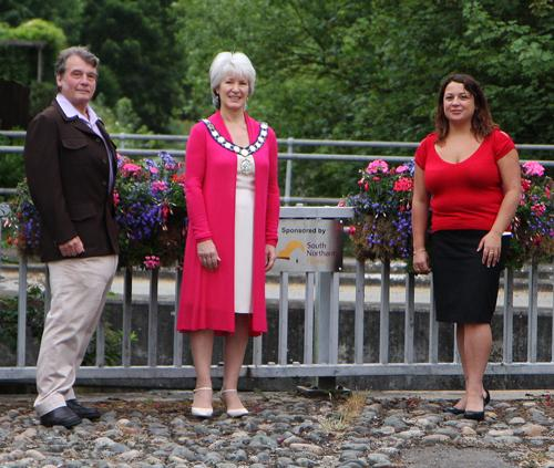 Roger Kightley Chair of SNH communications forum, left, The Mayor of Towcester Jacqueline Hart and right Becky Pavey, Community Development Manager at South Northants Home on the bridge with the blooms