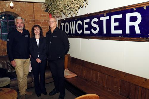 Pictured with the station sign is l-r John Evans from Towcester Mill Brewery, Sally Willett from Towcester Museum and Nigel Furniss from the SMJ Society