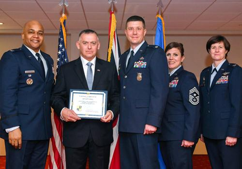 RAF Croughton, England – U.S. Air Force Colonel Ron Cheatham (left), 501 Combat Support Wing Vice Commander, Lieutenant Colonel Ray Elmore (centre), 422 Civil Engineer Squadron Commander, Chief Master Sgt. Lori Gawan (centre right), 501 Combat Support Wing Command Chief Master Sergeant, Colonel Bridget McNamara (right), 422 Air Base Group Commander, present Mr. Gary Crook (centre left), Community Safety and Emergency Planning Officer, with a certificate of appreciation after inducting him as an Honorary Commander at RAF Croughton on March 29, 2019. (U.S. Air Force photo by Senior Airman Chase Sousa).