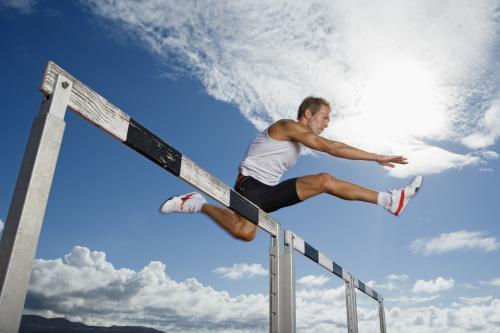 Man jumping a hurdle on an althetics race track