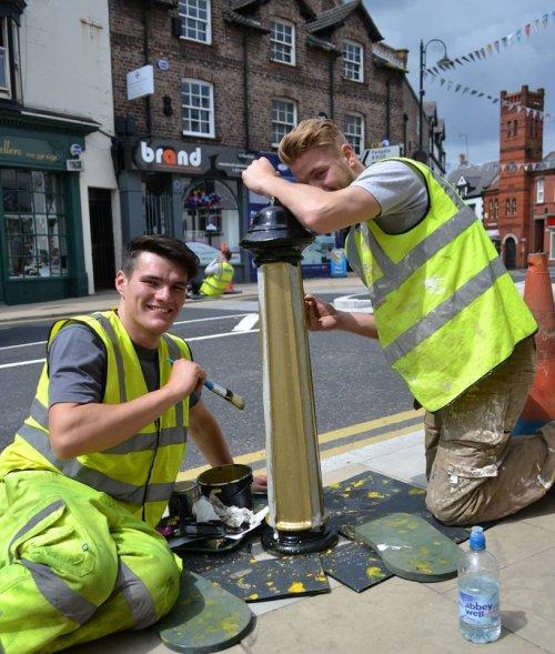 Final coat on the bollards in Neston town centre